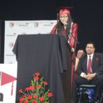 A graduate in a red robe and cap stands on stage behind a podium delivering a commencement address as faculty look on